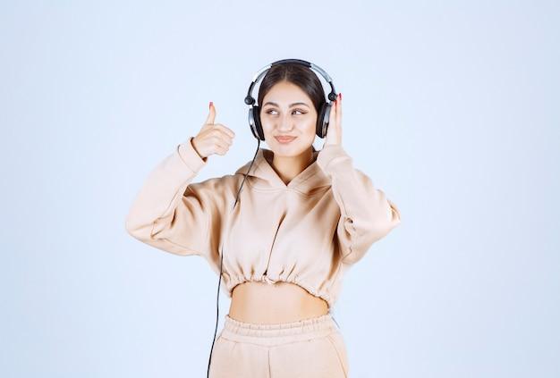 Mulher jovem ouvindo fones de ouvido e mostrando o polegar