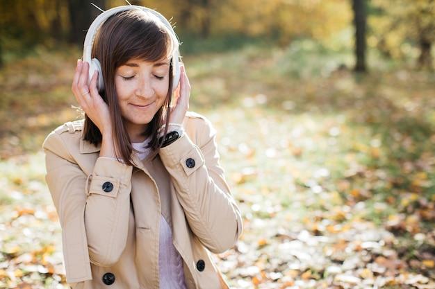 Mulher jovem ouvindo música com fones de ouvido na floresta de outono