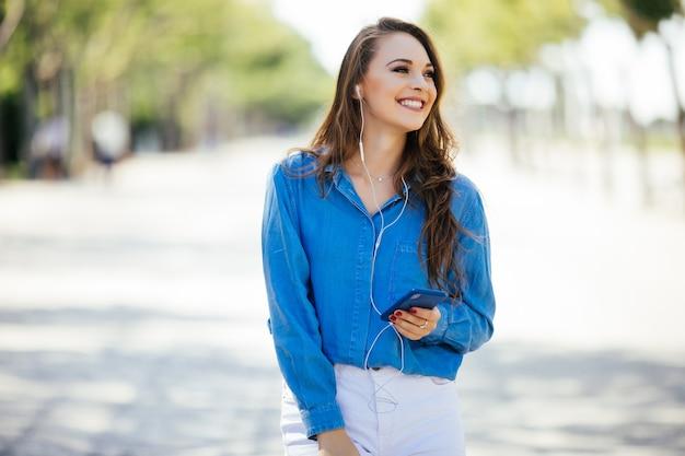 Mulher jovem ouvindo música com fones de ouvido na rua de verão