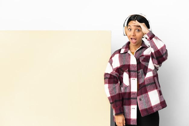 Mulher jovem ouvindo música com um grande cartaz vazio sobre um fundo isolado fazendo gesto de surpresa enquanto olha para o lado
