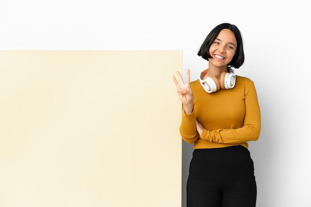 Mulher jovem ouvindo música com um grande cartaz vazio sobre um fundo isolado feliz e contando três com os dedos