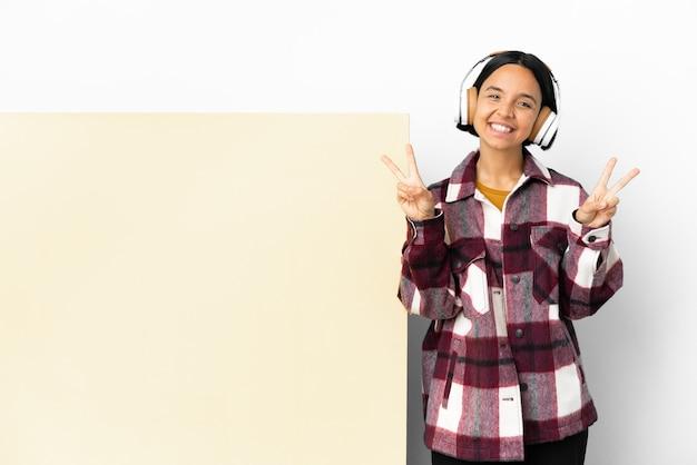 Mulher jovem ouvindo música com um grande cartaz vazio sobre um fundo isolado, mostrando o sinal da vitória com as duas mãos