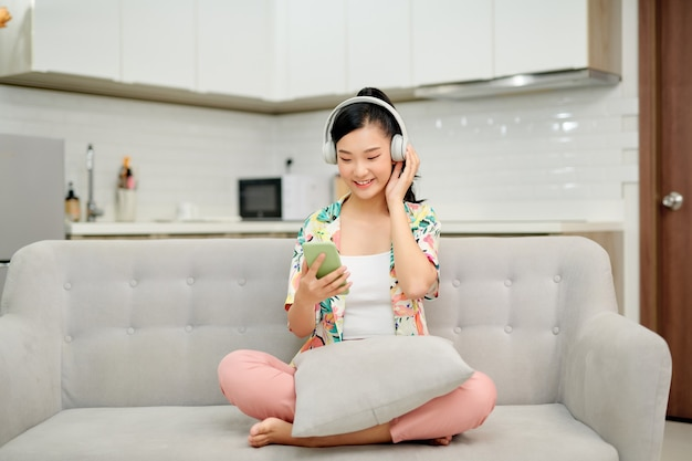 Mulher jovem ouvindo música enquanto relaxa no sofá em casa