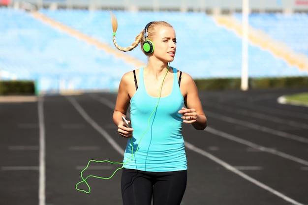 Mulher jovem ouvindo música no estádio