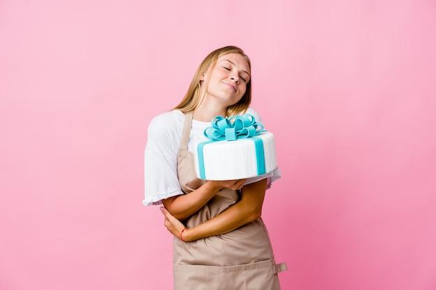 Mulher jovem padeiro russo segurando um delicioso bolo abraços, sorrindo despreocupada e feliz.