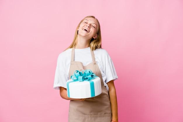 Mulher jovem padeiro russo segurando um delicioso bolo relaxado e feliz rindo, pescoço esticado, mostrando os dentes.