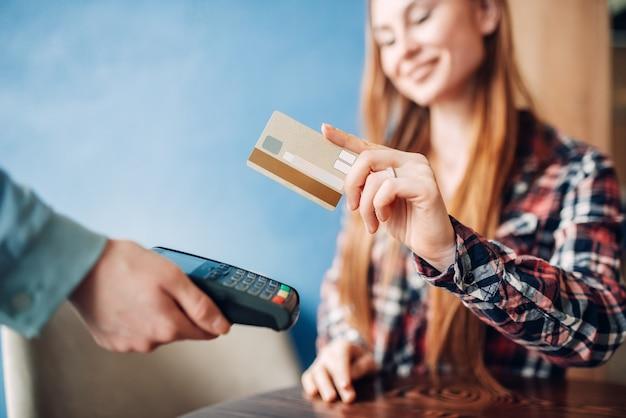 Mulher jovem pagando com cartão de crédito em um café