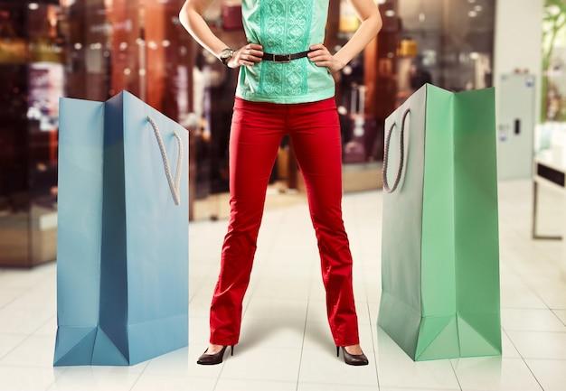 Mulher jovem parada entre duas grandes sacolas de compras no shopping