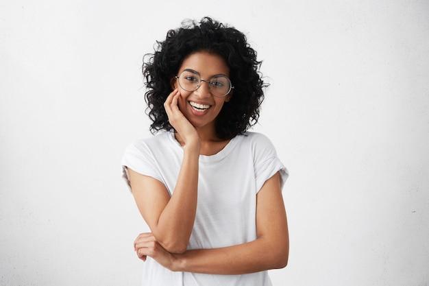 Mulher jovem parda de aparência amigável com cabelos cacheados cacheados e sorrindo alegremente