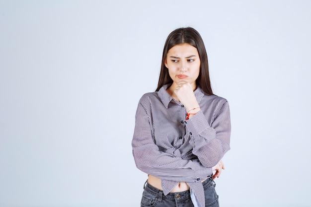 Mulher jovem parece pensativa e com brainstorming