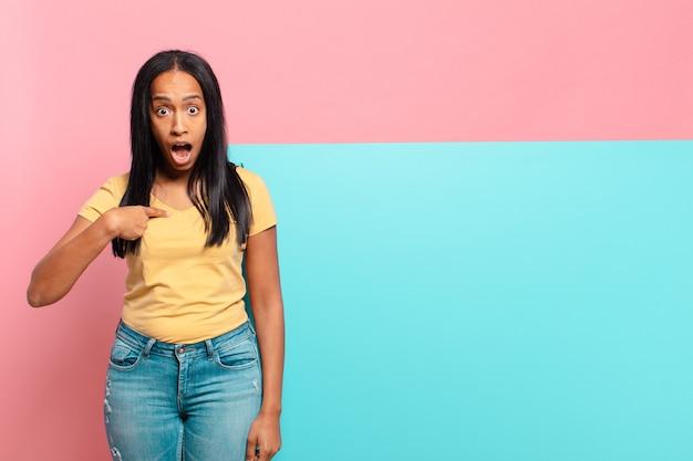 Mulher jovem parecendo chocada e surpresa com a boca bem aberta, apontando para si mesma