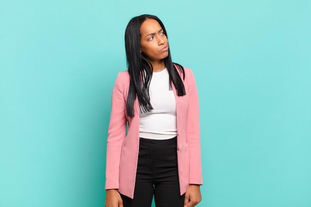 Mulher jovem parecendo perplexa e confusa, pensando ou tentando resolver um problema ou pensando