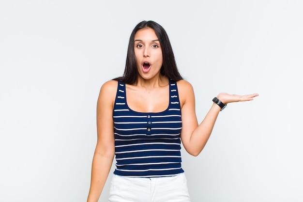 Mulher jovem parecendo surpresa e chocada, com o queixo caído segurando um objeto com a mão aberta na lateral
