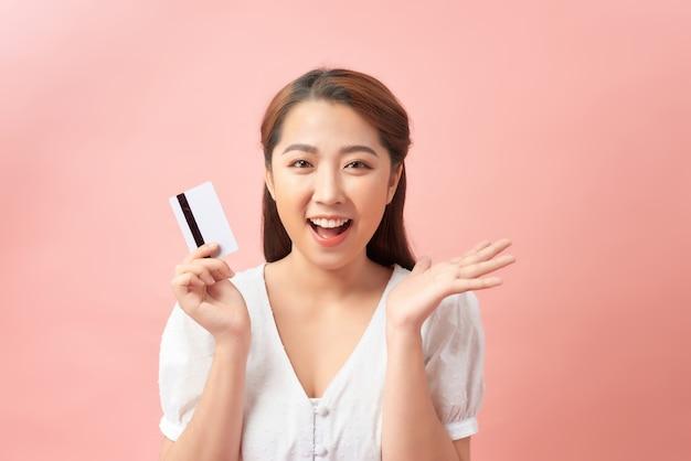 Mulher jovem parecendo surpresa e chocada, com o queixo caído segurando um objeto com a mão aberta segurando um cartão de crédito