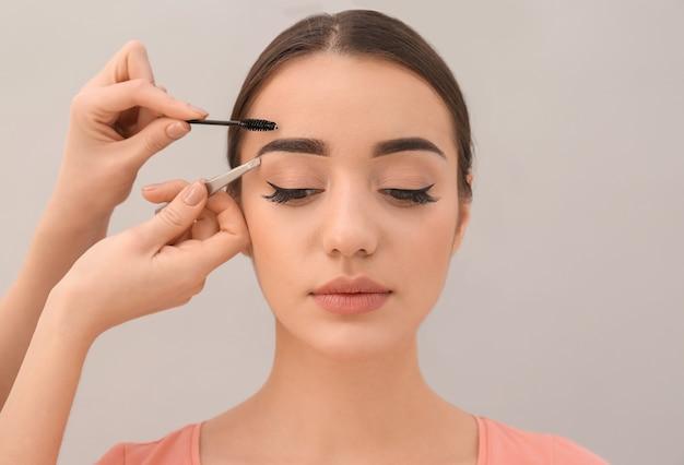 Mulher jovem passando por procedimento de correção de sobrancelha em fundo claro
