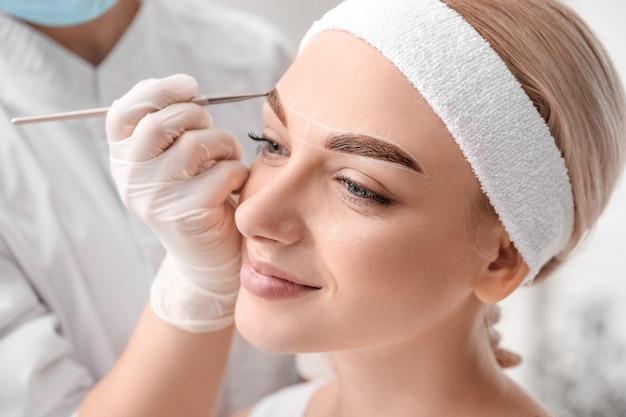Mulher jovem passando por procedimento de correção de sobrancelha em salão de beleza