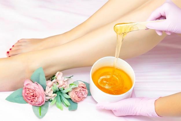 Mulher jovem passando por procedimento de depilação na perna com pasta de açúcar no salão