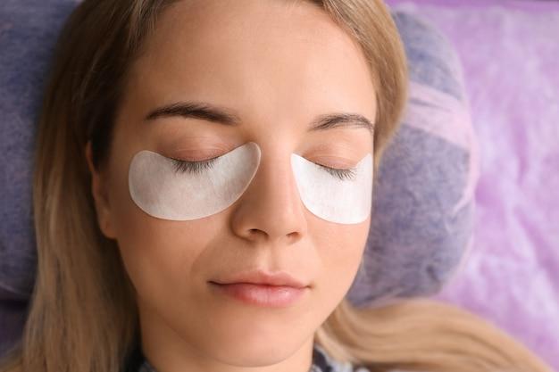 Mulher jovem passando por procedimento de extensão de cílios, close-up