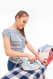 Mulher jovem passando suas roupas