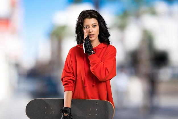 Mulher jovem patinadora sussurrando algo ao ar livre