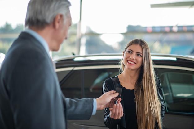 Mulher jovem pegando as chaves de seu carro em um showroom