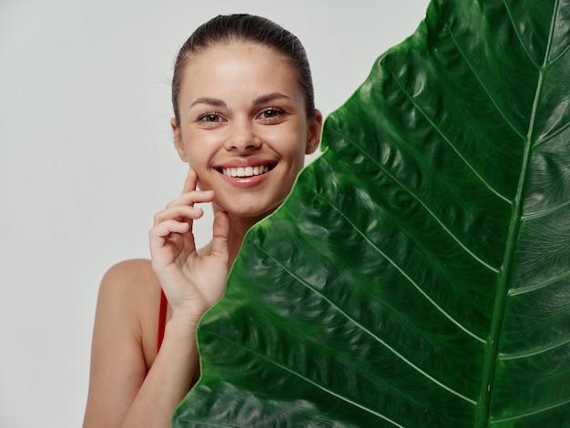 Mulher jovem, pele limpa, folha de palmeira verde, aparência natural, modelo de cosmetologia