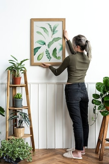 Mulher jovem pendurando uma moldura de pintura com folha impressa na parede