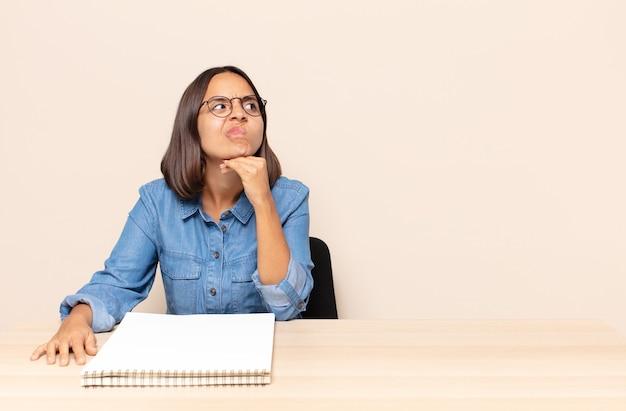 Mulher jovem pensando, sentindo-se duvidosa e confusa, com opções diferentes, imaginando qual decisão tomar