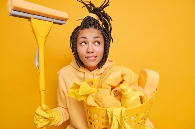 Mulher jovem pensativa, de pele escura, com capuz casual e luvas de borracha segurando o esfregão e o cesto de roupa suja
