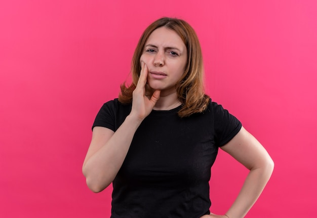 Mulher jovem pensativa e casual com as mãos na bochecha e na cintura em uma parede rosa isolada com espaço de cópia