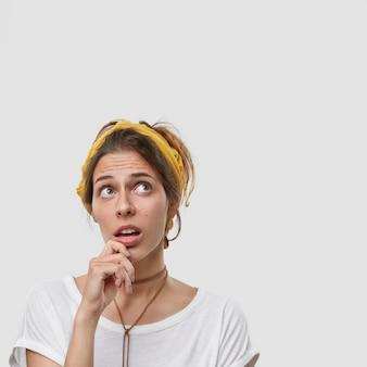 Mulher jovem, pensativa e intrigada, triste, com expressão facial preocupada, segura o queixo, olha para cima, pensa em algo, tem cabelo escuro