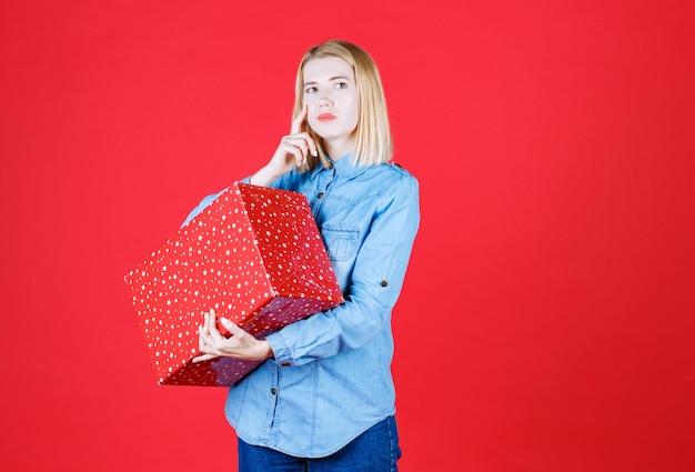 Mulher jovem pensativa em pé e segurando um presente na frente