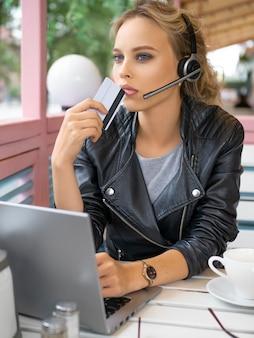 Mulher jovem pensativa no café com cartão de crédito em frente ao monitor do laptop