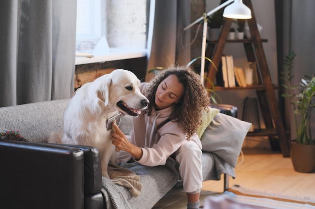 Mulher jovem penteando seu animal de estimação com um pente enquanto eles estão sentados no sofá da sala