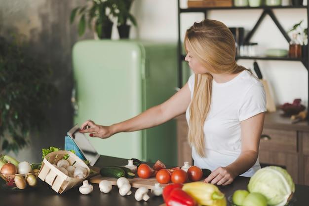 Mulher jovem, percorrendo, tablete digital, enquanto, preparando alimento
