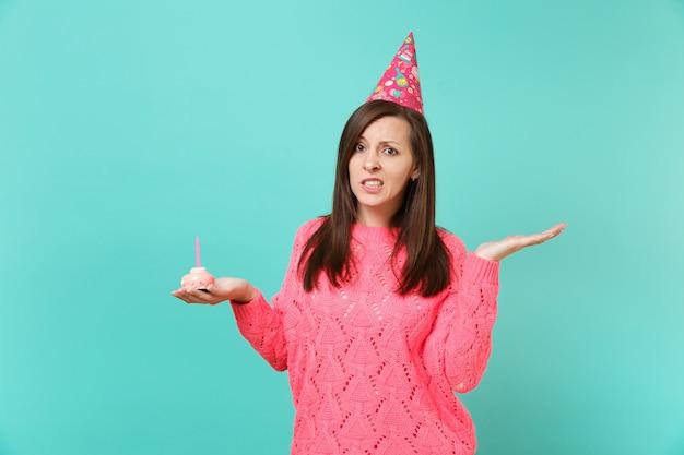 Mulher jovem perplexa no suéter de malha rosa, chapéu de aniversário apontando a mão de lado, segurando o bolo com vela isolada no retrato de estúdio de fundo de parede azul. conceito de estilo de vida de pessoas. simule o espaço da cópia.