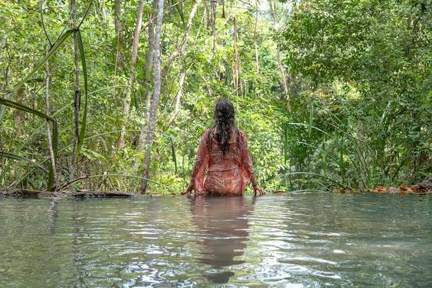 Mulher jovem perto de água turquesa da cascata na floresta tropical profunda, ilha de koh phangan, tailândia
