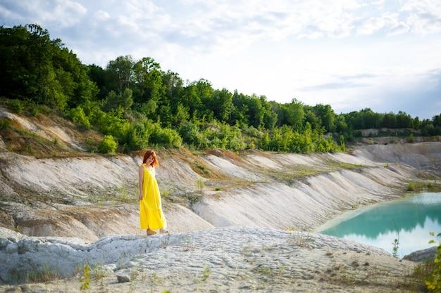 Mulher jovem perto de um lago com água azul e montanhas pedregosas com árvores verdes. bela vista do lago na floresta