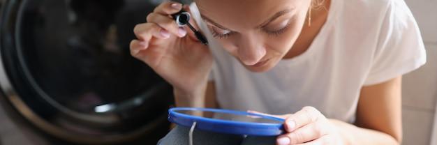 Mulher jovem pintando cílios com rímel em frente ao espelho do banheiro