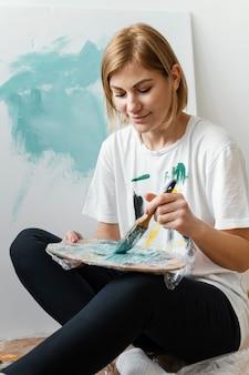 Mulher jovem pintando com acrílico sobre tela