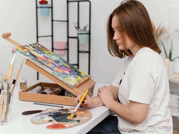 Mulher jovem pintando com acrílico