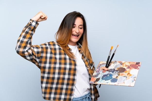Mulher jovem pintor sobre parede azul isolada, comemorando uma vitória