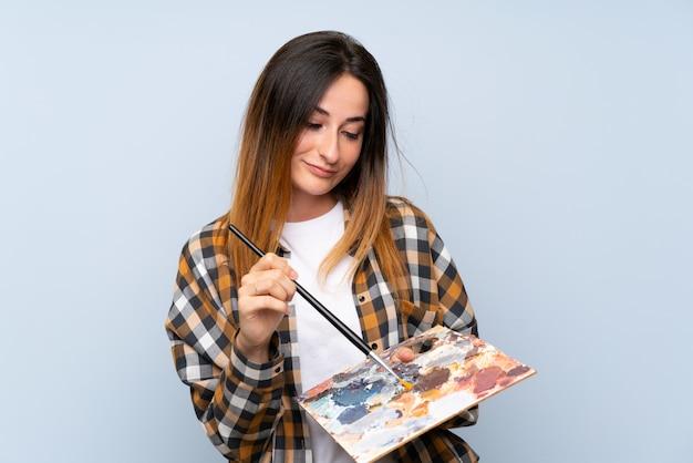 Mulher jovem pintor sobre parede azul isolada