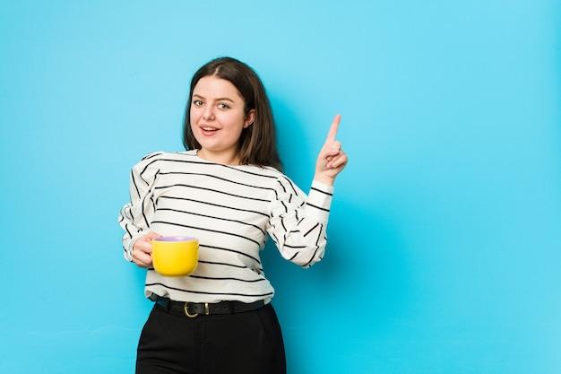 Mulher jovem plus size segurando uma caneca de chá sorrindo alegremente, apontando com o dedo indicador para longe.