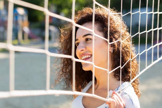 Mulher jovem posando ao lado de um campo de vôlei ao ar livre