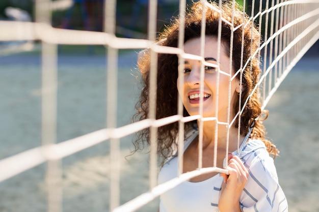 Mulher jovem posando ao lado de um campo de vôlei do lado de fora