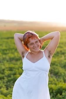 Mulher jovem posando com confiança ao ar livre em um campo e mostrando pelos nas axilas