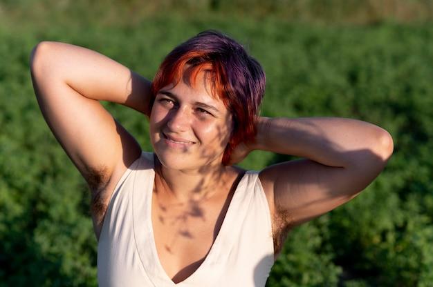 Mulher jovem posando com confiança e mostrando pelos nas axilas