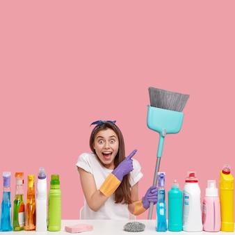 Mulher jovem posando com produtos de limpeza