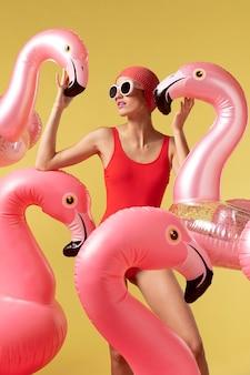 Mulher jovem posando com ringue de flamingo